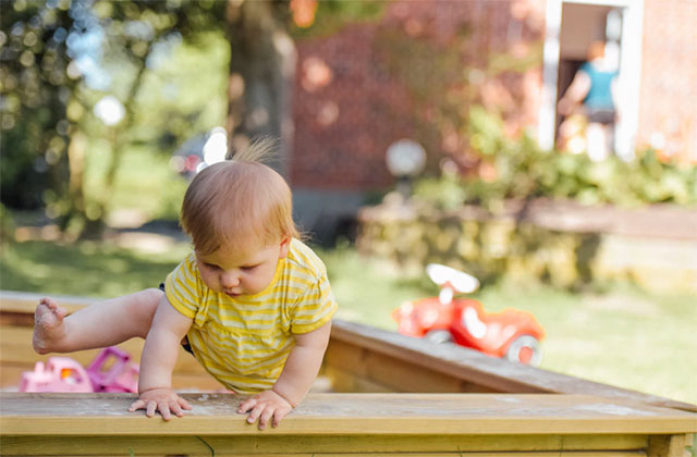 Baby climbing over the bench