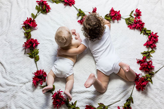 Two babies surrounded with red petaled flowers